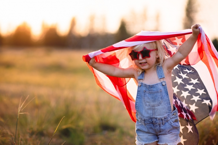 Little girl withe star glasses, american flag, and overalls