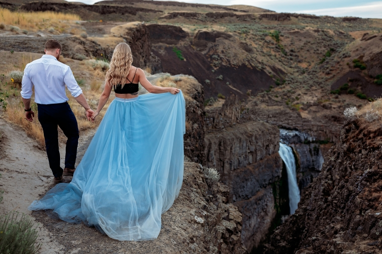 couple walking along a cliff in blue elopement gown